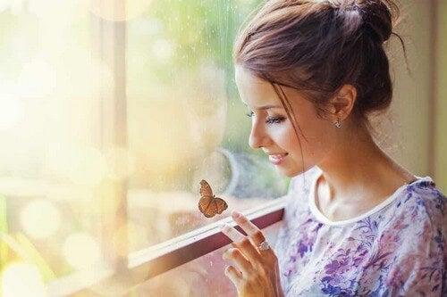 Donna alla finestra tocca una farfalla.