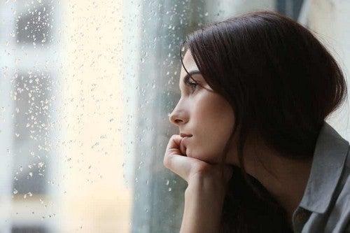Una donna triste che guarda dalla finestra.