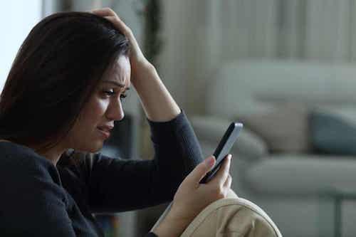 Ansia sociale e nuove tecnologie. Ragazza ansiosa mentre guarda il telefono.