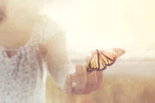 Donna che tiene una farfalla con le dita della mano.