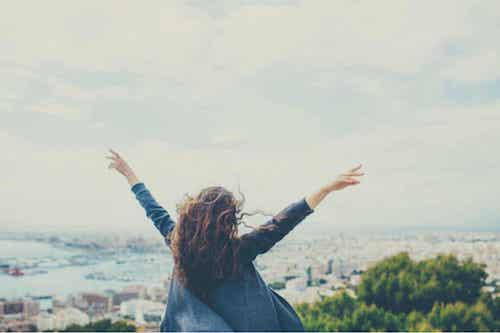 L'importanza di piacersi e accettarsi. Donna felice con le braccia verso il cielo.