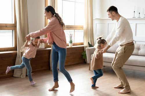 Padre e madre che ballano con le figlie.