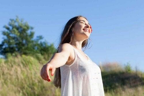 Giovane donna sorride al sole.