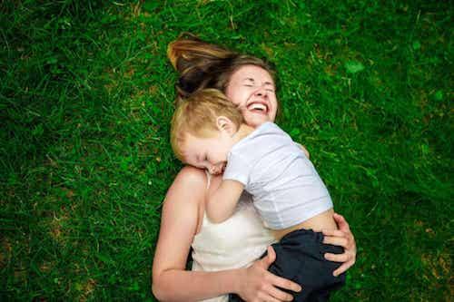 Madre sdraiata su un prato che abbraccia sui figlio. Madre e figlio abbracciati che ridono.