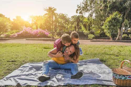 Madre e figli che fanno un picnic e si divertono.