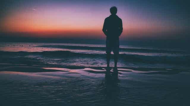 Uomo di fronte al tramonto sul mare.