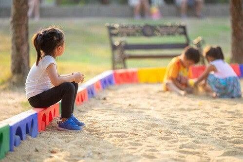 Bambina che guarda gli altri bambini che giocano.