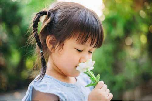 Bambina che odora un fiore.
