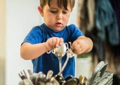 Bambino che pulisce le posate.
