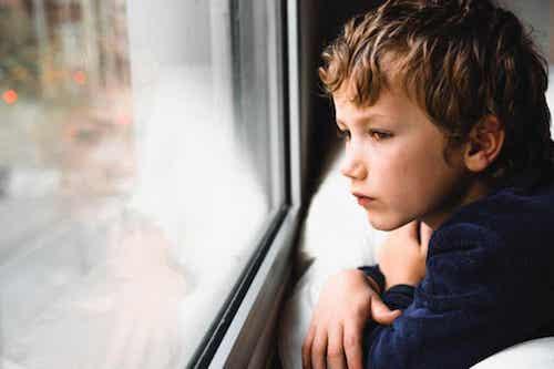 Bambino pensieroso che guarda dalla finestra.