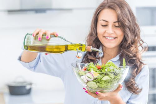 Donna che condisce l'insalata con dell'olio extravergine di oliva.