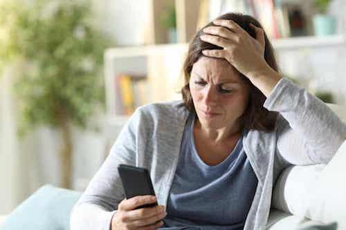 Donna preoccupata dalle notizie negative che legge sul telefono.