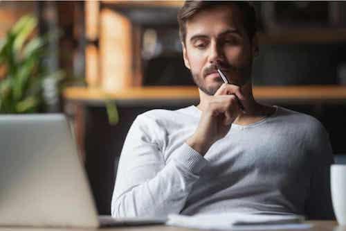 Uomo che pensa mentre lavora al computer.